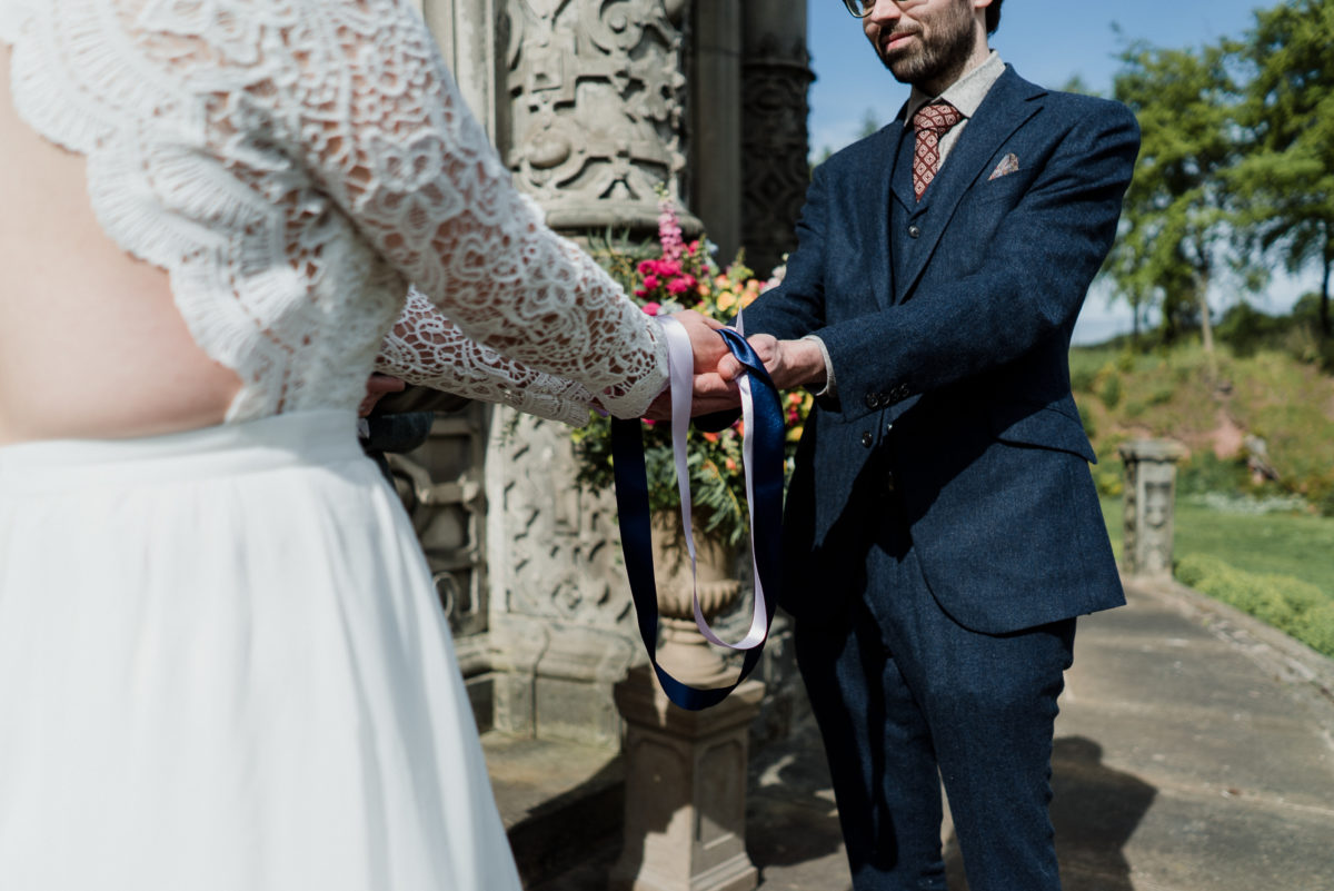 Handfasting at an outdoor wedding ceremony by the Orangerie at Restoration Yard, Dalkeith Country Park