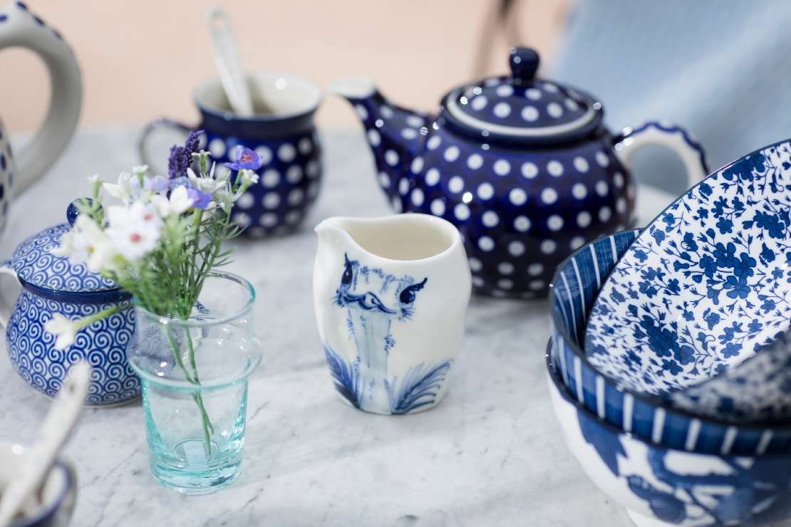 Blue and white Artyfarty, Mia Sarosi, ECP crockery with faux flowers on a marble table